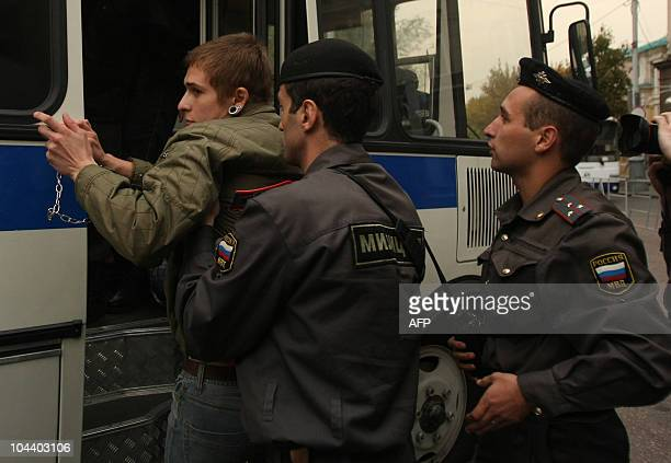 Police officers escort a gay rights activists detained during a protest against homophobic policies of the Russia's capital authorities in front of...