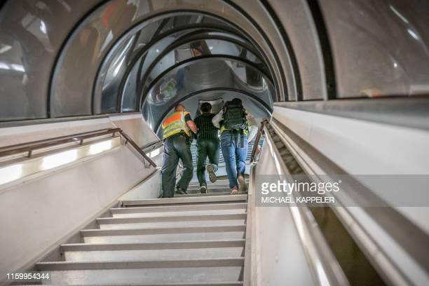 TOPSHOT Police officers escort a rejected Afghan asylum seeker as they board an aircraft heading to Kabul on August 1 2019 at an airport in Leipzig...