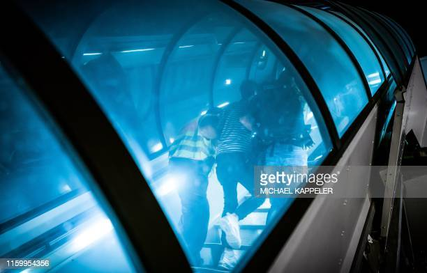 Police officers escort a rejected Afghan asylum seeker as they board an aircraft heading to Kabul, on August 1, 2019 at an airport in Leipzig,...