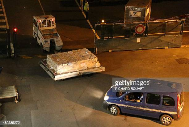Police officers escort an airport vehicle transporting what is believed to be debris from a Boeing 777 plane that washed up on an Indian Ocean island...