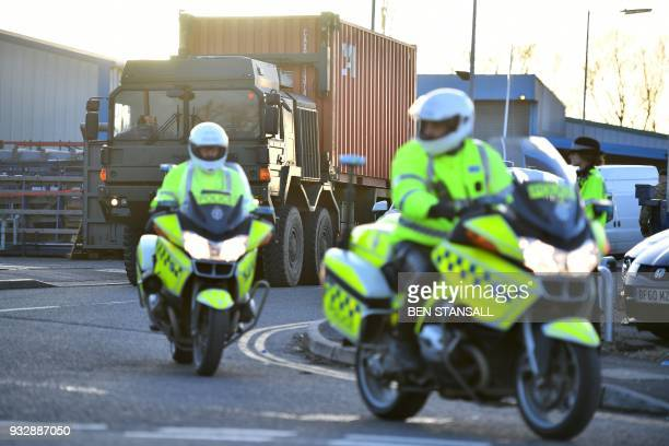 Police officers escort an army truck carrying a freight container laden with the car of Sergei Skripal as it is driven from the Churchfields...