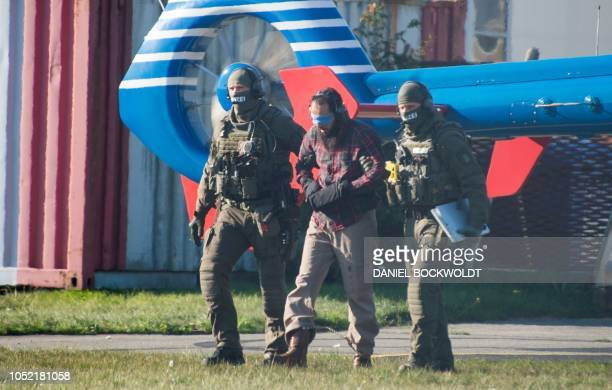 TOPSHOT Police officers escort Moroccan terror accomplice Mounir el Motassadeq after he was brought with a helicopter from the Fuhlsbuettel prison...