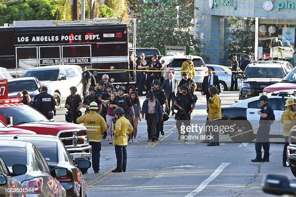 TOPSHOT Police officers escort people after a suspect barricaded inside a Trader Joe's supermarket in Silverlake Los Angeles on July 21 2018 A...
