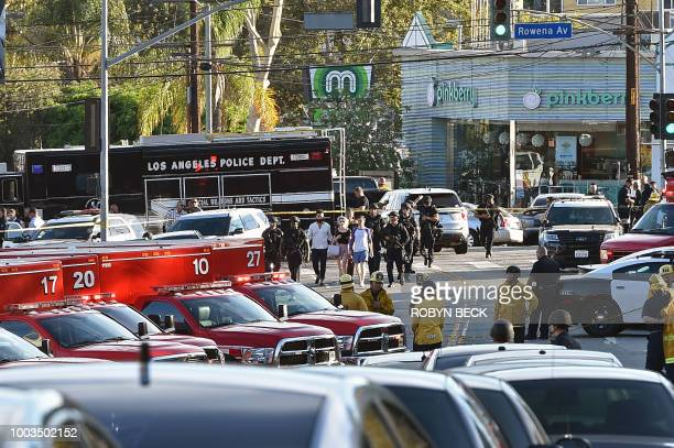 Police officers escort people after a suspect barricaded inside a Trader Joe's supermarket in Silverlake Los Angeles on July 21 2018 A suspect wanted...