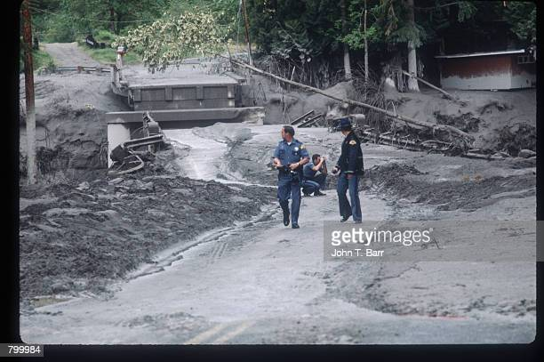 Police officers examine the ash covered landscape May 23 1980 in Washington State On May 18 an earthquake caused a landslide on Mount St Helens''...