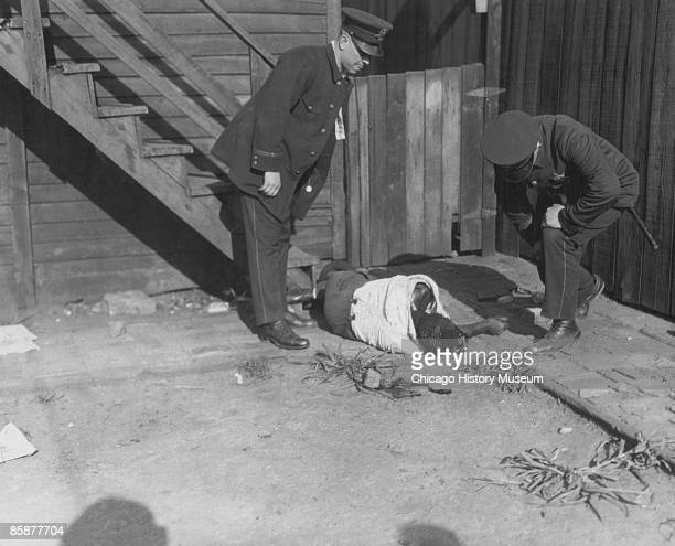 Police officers examine the corpse of an African American man who had been stoned and beaten to death during the Chicago race riots July 1919