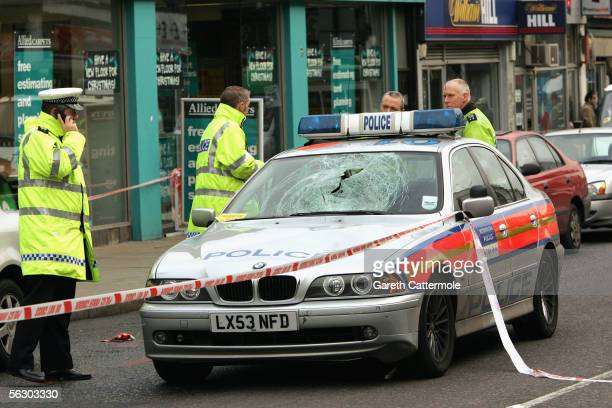 Police officers examine the scene of a road traffic accident where a police car responding to an emergency call collided with a pedestrian November...