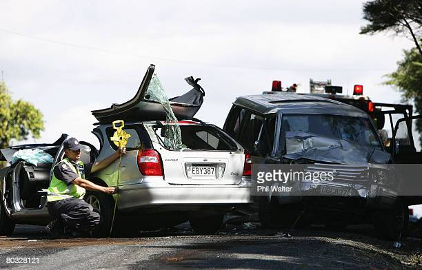 Police officers examine the scene where four people were killed in a road accident near Clevedon March 21 2008 in Auckland New Zealand The deaths...