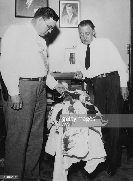 Police officers examining the bloodstained clothing of outlaw John Dillinger on the day he was shot and killed by police and federal agents in...