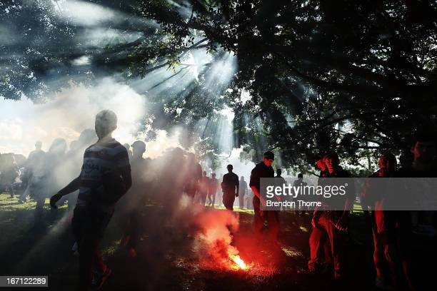 Police officers extinguish a flare as Western Sydney Wanderers fans walk to the stadium before the ALeague 2013 Grand Final match between the Western...