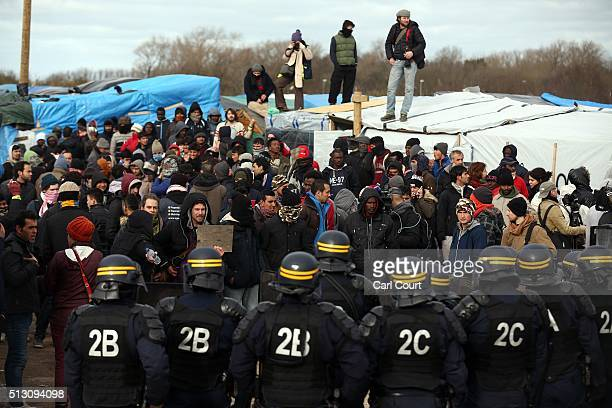Police officers face activists and migrants as part of the 'jungle' migrant camp is cleared on February 29 2016 in Calais France The French...