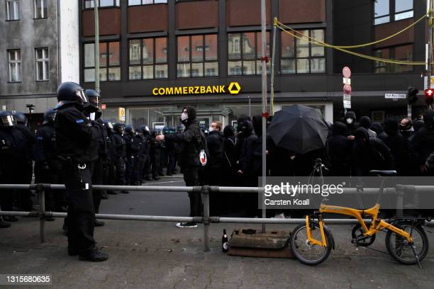 """Police officers face demonstrators participating in the annual """"Revolutionary May 1"""" leftist protest march on May Day during the third wave of the..."""