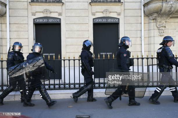 Police officers face protesters avenue Montaigne in Paris in front of luxury shop windows during a Yellow vest antigovernment demonstration on...