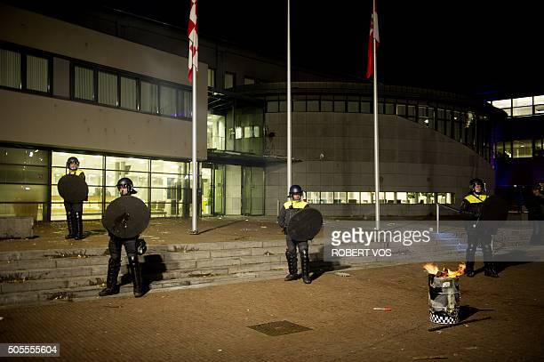 Police officers face protesters during a demonstration against the plans to open a refugee centre for 500 regufees in Heesch on January 18 2016 As...
