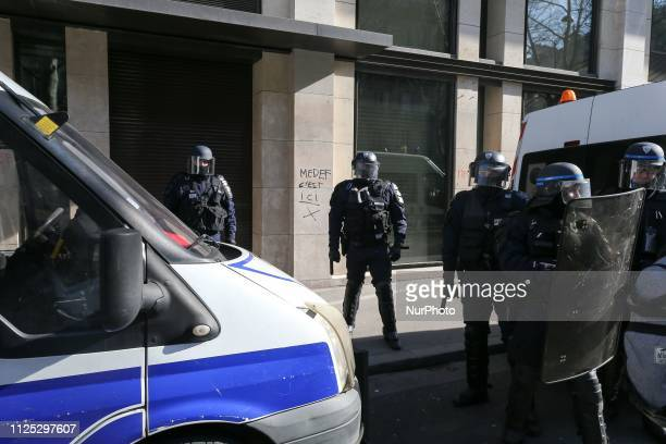 Police officers face protesters in front the French employers'association Medef's headquarters in Paris during a Yellow vest antigovernment...