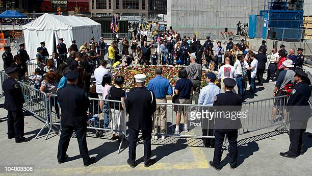 Police officers firemen and mourners surround a reflecting pool at Ground Zero during the annual 9/11 memorial service September 11 2010 in New York...