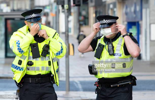 Police officers fit their masks as a precaution against the transmission of COVID-19 as they patrol by customers queuing outside the Primark store on...