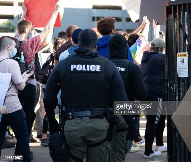 Police officers follow protesters to the lawn of the police station in Detroit, Michigan on May 31, 2020 following a night of protests that saw...