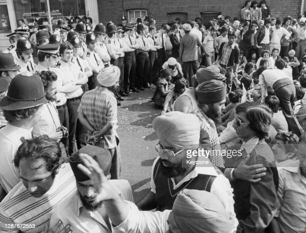 Police officers form a barrier between a sit-down demonstration by the Asian community and the police station in protest at the death of Sikh...