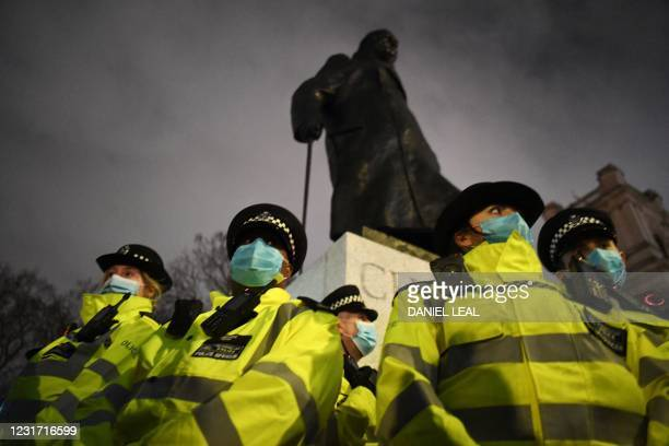 Police officers form a cordon around a statue of former prime minister Winston Churchill in Parliament Square in central London on March 14, 2021 as...
