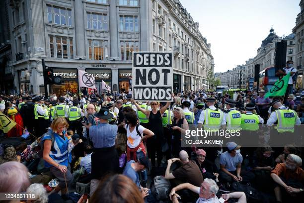 Police officers form a cordon around climate activists from the Extinction Rebellion group who are gathered around a structure they built blocking...