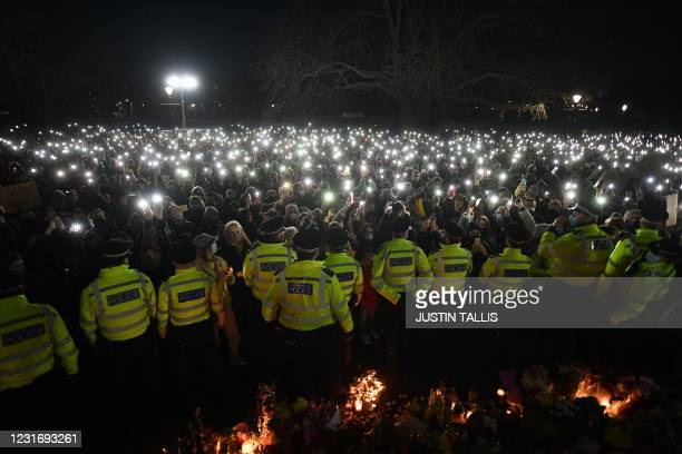 Police officers form a cordon as well-wishers turn on their phone torches as they gather at a band-stand where a planned vigil in honour of alleged...
