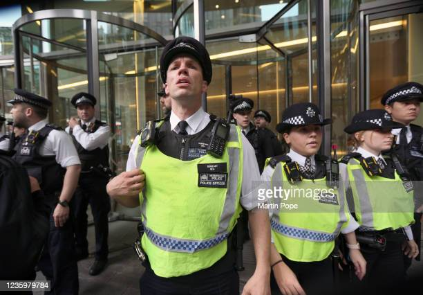 Police officers form a cordon at Bill and Melinda Gates Foundation building on October 19, 2021 in London, England. Protesters from Official Voice...