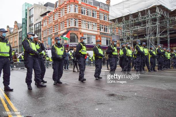 Police officers form a cordon to keep pro-Israel and pro-Palestine protesters apart in Kensington High Street during the rally. Protesters gathered...