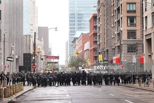 Police officers form a line to hold back demonstrators protesting the G8/G20 summits on June 26, 2010 in Toronto, Ontario Canada. Store windows were...