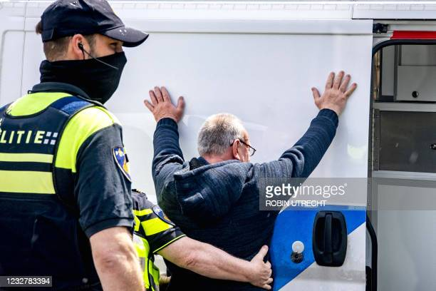 Police officers frisk a man, prior to the Eredivisie soccer match between Feyenoord and Ajax at the Feyenoord Stadium in Rotterdam on May 9, 2021. -...