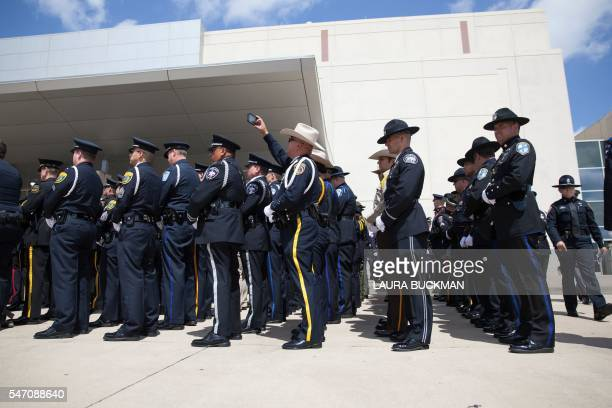 TOPSHOT Police officers from around Texas wait for the casket of Officer Brent Thompson to be escorted out of the memorial service at The Potter's...
