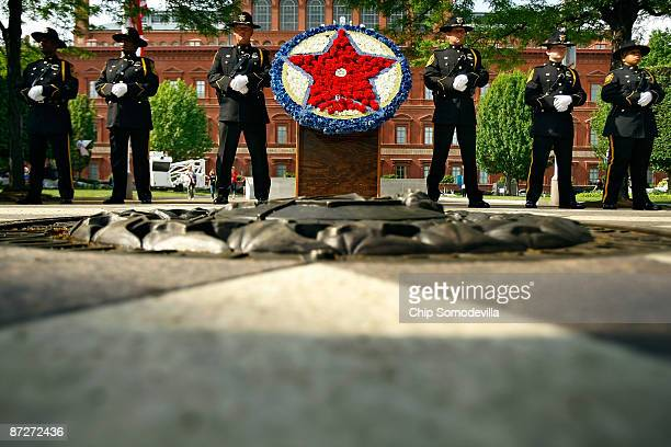 Police officers from Dekalb County Georgia stand watch next to the flower wreath that stands in the middle of the National Law Enforcement Officers...