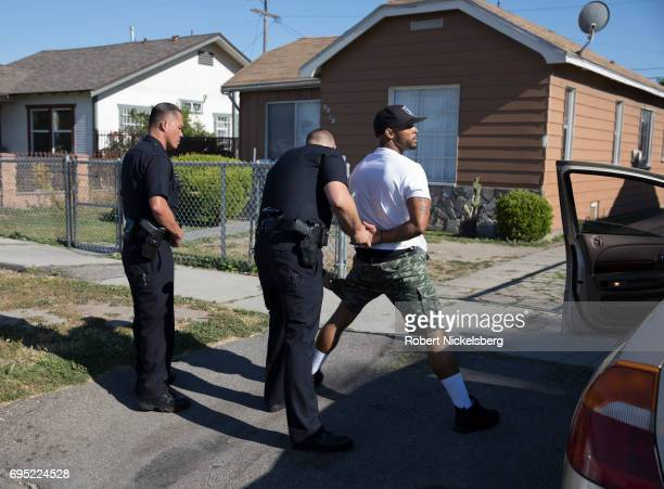 Police officers from the 77th Division gang unit handcuff a man who had been stopped in his car May 21 2017 for a vehicle code violation in Los...