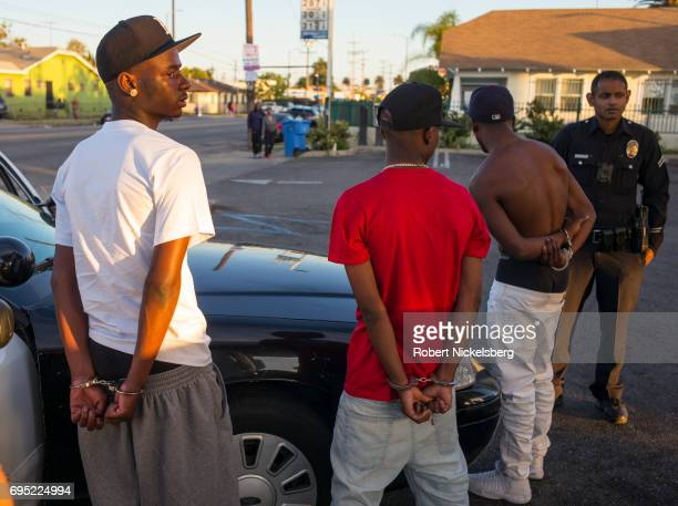 Police officers from the 77th Division gang unit handcuff three men who had been stopped in their car May 21 2017 for a vehicle code violation in Los...