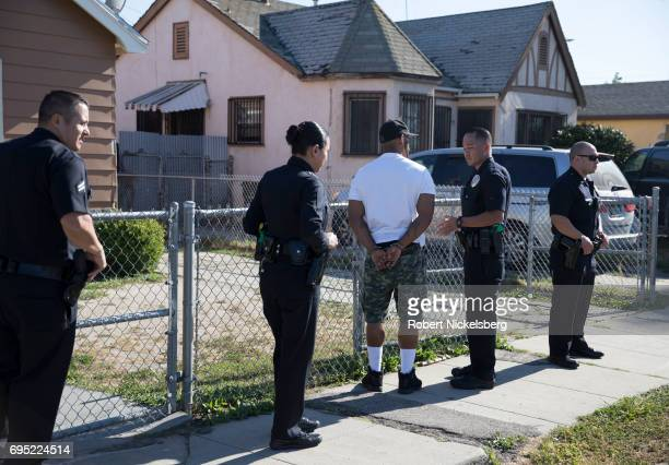 Police officers from the 77th Division gang unit question a man who had been stopped in his car May 21 2017 for a vehicle code violation in Los...