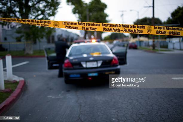 Police officers from the Los Angeles Police Department Counter Surveillance Team and gang units seal off a street and take into custody two Bloods...