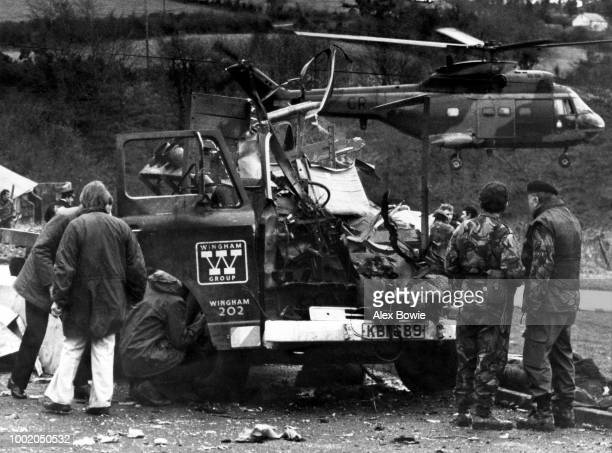 Police officers from the Royal Ulster Constabulary and soldiers from the 2nd Battalion Royal Green Jackets examine the wreckage of a lorry severely...