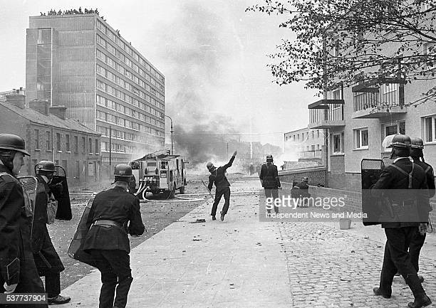 Police officers from the Royal Ulster Constabulary face off with Bogside residents atop the Rossville Flats tower block during the Battle of the...