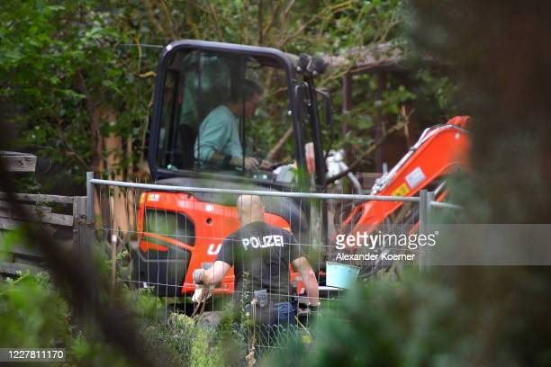 Police officers from the state police of North Rhine-Westphalia use a digger on an allotment garden on July 28, 2020 in Hanover, Germany. German...