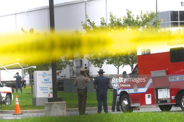 Police officers gather below crime scene tape in front of a Rite Aid Distribution Center where multiple people were killed and injured in a shooting...