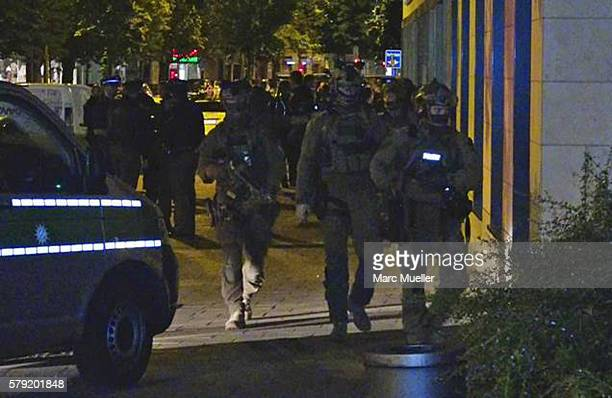 Police officers gather outside the suspect's home July 23 2016 in Munich Germany According to policeten people were killed in a shooting the evening...