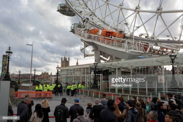 Police officers gather under the London Eye lockeddown after four people were killed and 20 injured during a terrorist attack on Westminster Bridge...