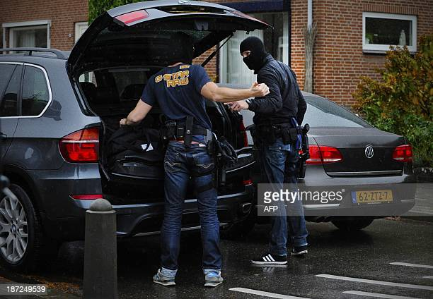 Police officers get ready to intervene on November 7 2013 in the Limburg village of Reuver where a shooting occurred According to witnesses a woman...