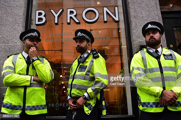 Police officers guard a Byron burger restaurant as protesters demonstrate outside on August 1 2016 in London England Protesters are opposing an...