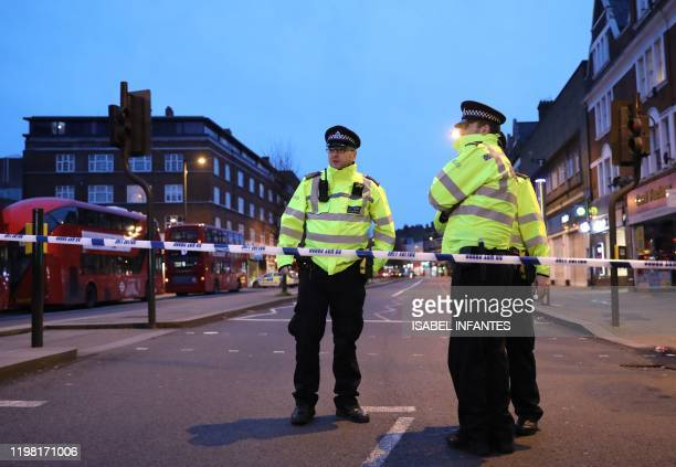 Police officers guard a cordon, set up on Streatham High Road, at the junction of Woodbourne Road, in south London on February 2 after a man is shot...