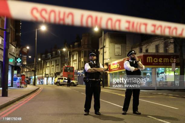 Police officers guard a cordon set up on Streatham High Road at the junction of Prentis Road in south London on February 2 after a man is shot dead...
