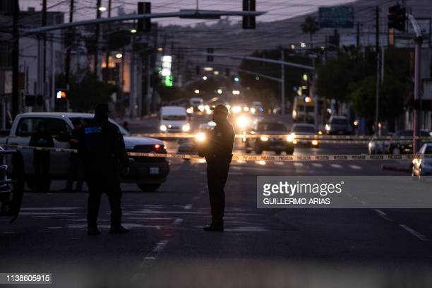 TOPSHOT Police officers guard a crime scene where a man was killed by gun fire in downtown Tijuana Baja California state Mexico on April 21 2019...