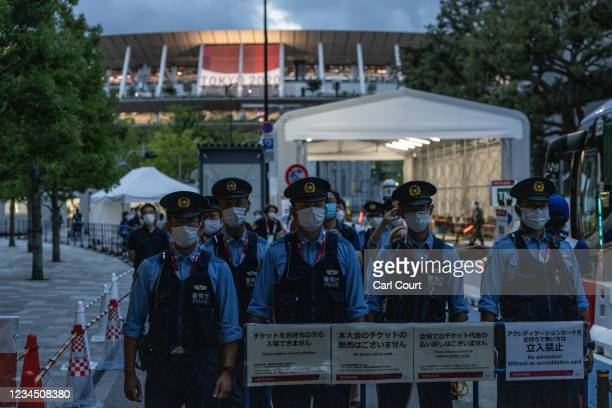Police officers guard an entrance to the Olympic Stadium as an anti-Olympics protest takes place nearby on August 6, 2021 in Tokyo, Japan. Fans have...