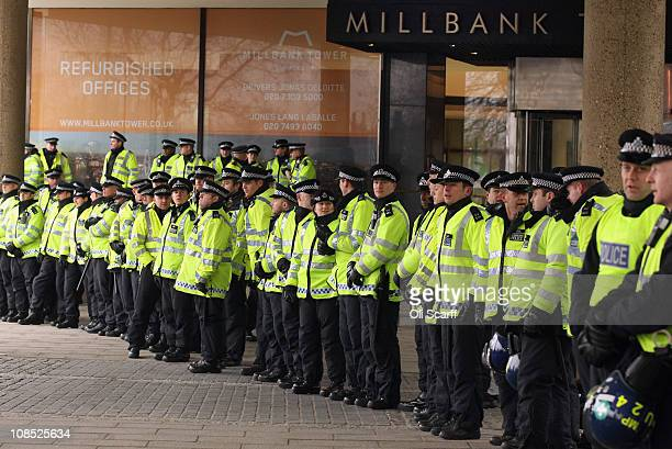 Police officers guard Millbank Tower as student demonstrators march to Parliament to protest against the Government's cuts to public services and an...
