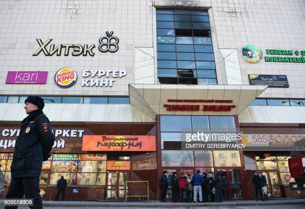Police officers guard outside a shopping mall gutted by a fire in the industrial city of Kemerovo in western Siberia on March 29 2018 / AFP PHOTO /...